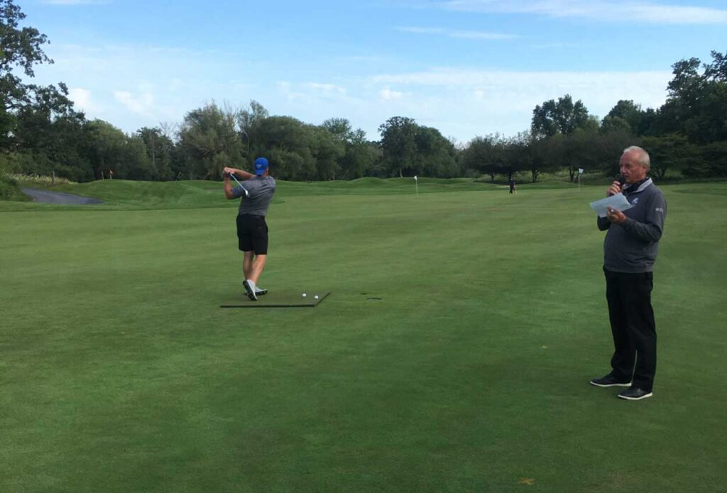 A golfer takes a swing at Black River golf course during charity event.
